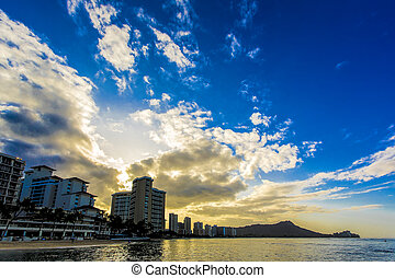Early morning sunrise illuminates the clouds and waters over Diamond Head and Waikiki Beach area of Oahu in Hawaii