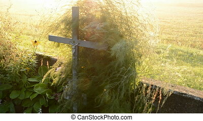 sunrise light and old crucifix on the field
