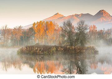 Sunrise light hits high mountains peaks in Tatra mountains