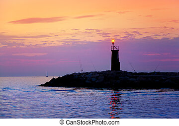Sunrise lighthouse glowing in blue purple sea