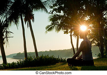 Sunrise Meditation - A young woman siting on grass ...