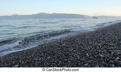 Sunrise, morning over sea with foamy waves against pebbles on a beach, coast
