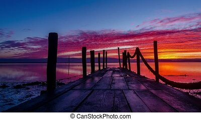 Sunrise of a wooden pier over a lake.