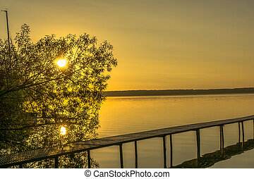 Sunrise on a lake with moorings for boats
