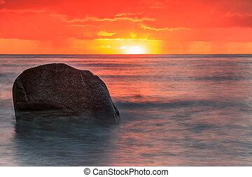 Sunrise on coastline of the Baltic Sea with stone