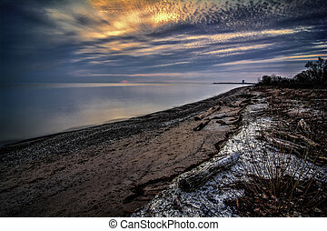 Beautiful sunrise over Lake Erie from Magee Marsh in Northwest Ohio. Davis-Besse nuclear power plant can be seen in the distance. The foregrround has driftwood and Zebra Mussel shells on the beach.