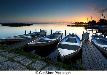 sunrise on lake harbor with boats
