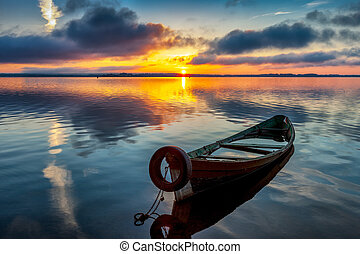 Sunrise on Lake Seliger with an old boat in the foreground.