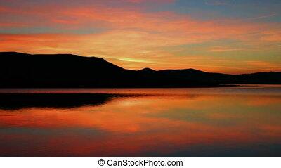 sunrise on morning lake with mountain
