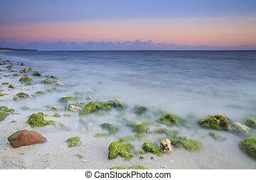Sunrise on rocky ocean beach