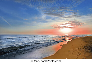 Sunrise on sandy beach. Lot of reflexions i wet coast and...