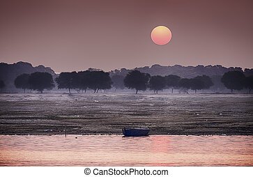 The sun rises over the eastern riverbank of the Ganges River near Varanasi, India.