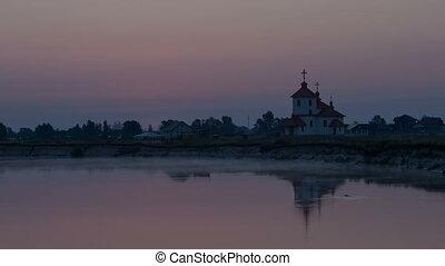 sunrise on the river near the church