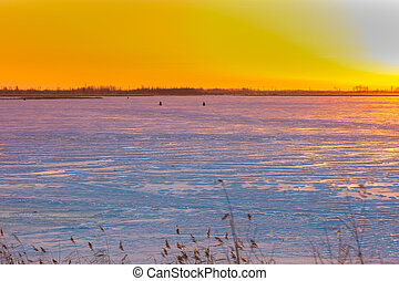 Sunrise over the river covered with ice and snow