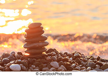Sunrise on the sea and the pyramid of pebbles