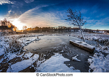 Sunrise on winter lake covered with snow