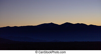 Sunrise or sunrise over mountains silhouette with blue sky background. Panoramic view, banner.
