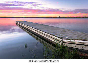 Sunrise or sunset on a fishing dock with colorful clouds reflecting in the lake