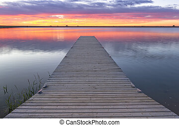 sunrise or sunset over a fishing dock with colorful clouds reflecting in the lake