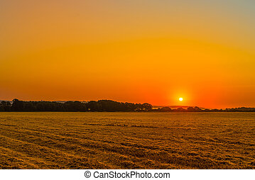 Sunrise over a countryside field