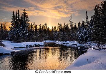 Sunrise over a creek in winter