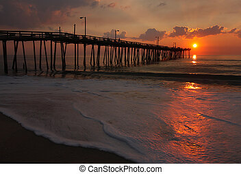 Rays from the rising sun illuminate a fishing pier, the ocean and foam from a beach in Nags Head, North Carolina
