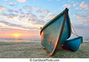 Sunrise over an two wooden fishing boats