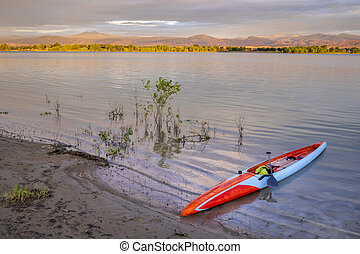 sunrise over Boyd Lake and Front Range of Rocky Mountains with a long stand up paddleboard
