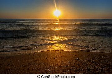 Sunrise over calm sea and sandy shore