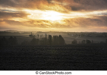 Sunrise over cold foggy autumn morning landscape