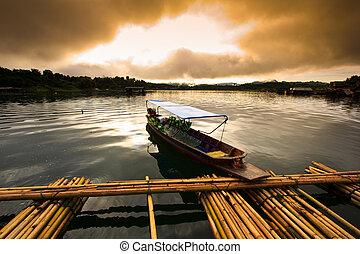 Sunrise over dam at port and fishing boat in Kanchanaburi...