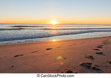 Sunrise over footprints on beach