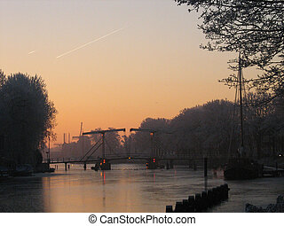 Sunrise over frozen river with bridge and windmills in...
