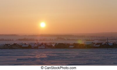 Sunrise over frozen snow-covered russian rustic landscape,...