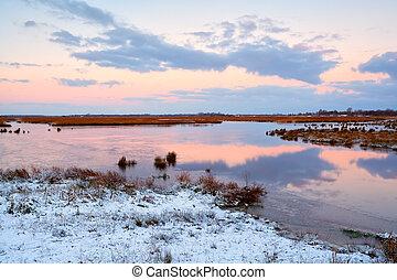 sunrise over frozen swamp in winter
