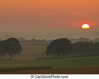 sunrise over hilly farmland