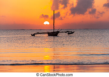 Sunrise over Indian ocean. Wooden boat on the beach of Mombasa with beautiful sunrise on the background.