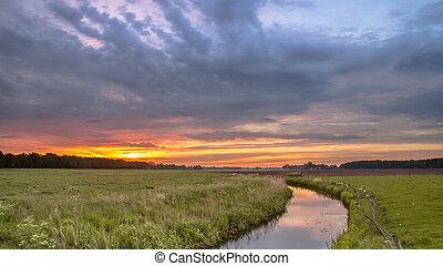 Sunrise over lowland river valley landscape