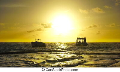 Sunrise over ocean waves. Two boats rock on the waves.