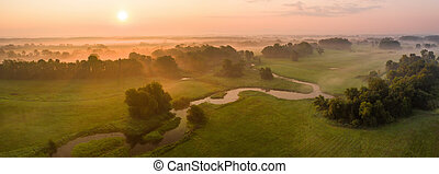 Sunrise over riparian forest with tortuous river meanders in...