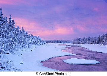 A rapid in a river in a wintry landscape. Photographed at the Äijäkoski rapids in the Muonionjoki river in Finnish Lapland at sunrise.