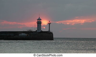 Sunrise over the Black Sea against a beacon in Yalta, a view from the central embankment, the Crimea