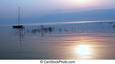 Boat floating on the calm water under amazing sunset. Sunrise over the lake.