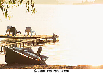 Sunrise over the lake with boat in dock and chairs on pier.