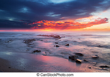 Sunrise over the ocean with rocks and water in foreground