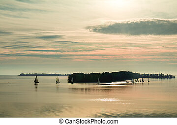 Sunrise over the river with yachts on a calm water surface