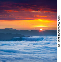 Sunrise over the sea of fog in the mountains at the summer