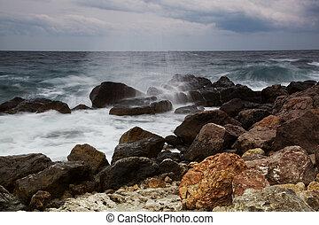 Sunrise over the sea. Waves break about coastal stones
