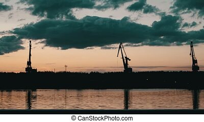 Sunrise over Volga-river and port cranes against sky -...