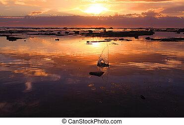 The splash of a small pebble against the amazing orange red red sunrise, Bateau Bay rockshelf reef at high tide, NSW Australia